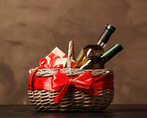 Geschenkkorb mit Geschenken und Weinflaschen dekoriert mit schoener roter Schleife