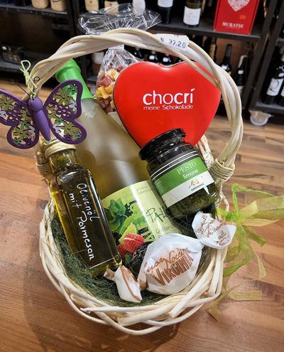 Geschenkkorb mit Grüntee-Litschi-Secco und Olivenöl sowie weiteren Delikatessen