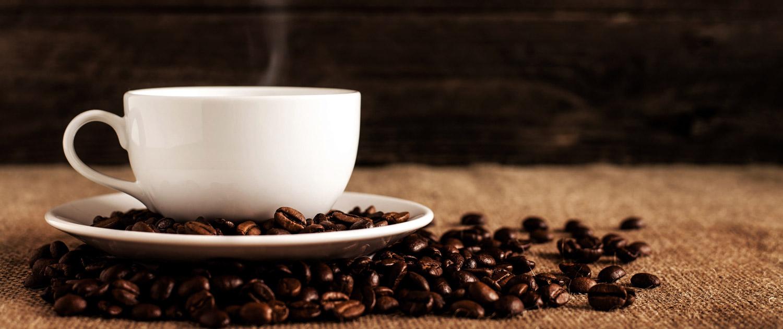 Weiße Kaffeetasse auf Holztisch mit Kaffeebohnen dekoriert